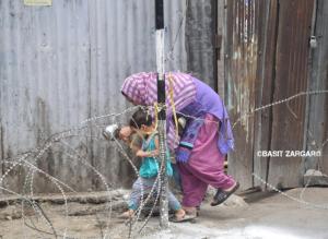 Woman with child crossing razor wire barrier (Basit Zargar) July 8 2017