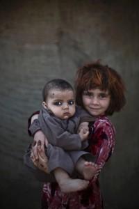 Khalzarin Zirgul (6) holds 3-month old cousing, Zaman (M.Muheisen) Oct 16 2015
