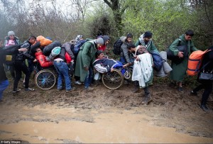 Refugees in wheelchairs fording river (Getty Images) Mar 17 2016