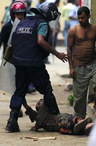 Dhaka policeman kicks striking child ( Munir Uz Zaman:AFP:Getty Images) 2010