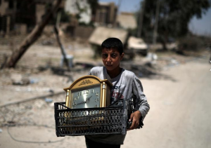 A displaced Iraqi boy carries a clock as he flees from western Mosul, Iraq. REUTERS:Alkis Konstantinidis June 1 2017