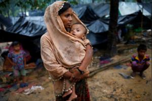 Ro mother & child in rain (Reuters: Mohammad Ponir Hossain)