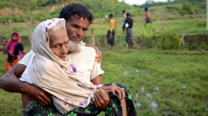 Rohingya man carrying mother after crossing into Bangladesh (CNN) Sept 5 2017