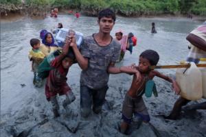 Ro man helping kids cross Naf (Adnan Abidi:Reuters) Nov 9 2017