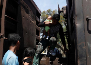 A Central American migrant holds a baby as he disembark from a freight train in Tlaquepaque, in Jalisco state, April 17, 2018. REUTERS:Edgard Garrido