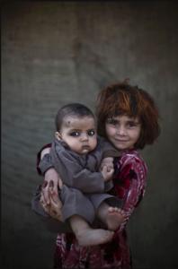 Khalzarin Zirgul, six, holds her cousin, three-month-old Zaman (M. Muheisen)