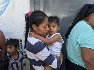 Asylum seeking mother holds her child in Tijuana, Apr 25, 2018. (Jean Guerrero:KPBS) Apr 30 2018